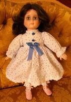 Szép arcú porcelán baba, kék mintás ruhában.