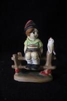Padon ülő porcelán fiú Hummel típusú figura