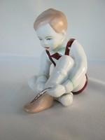 Aquincumi porcelán cipőt húzó kisfiú