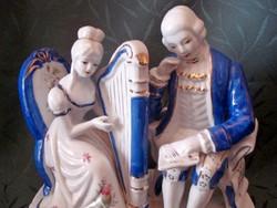 Barokk stílusú zenész pár hárfán játszó nő, kottát olvasó férfi