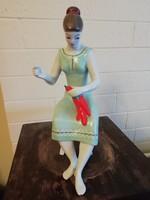 Hollóházi paprikát fűző ülő nő