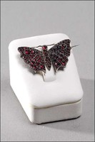Butterfly-shaped badge / art deco female jewelery set with art deco garnet stones at auction