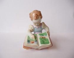 Herendi könyvet nézegető kislány jubileumi jelzéssel
