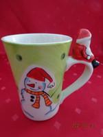 Karácsonyi porcelán bögre, hóember és karácsonyfa az oldalán, mikulás ül a fülén.