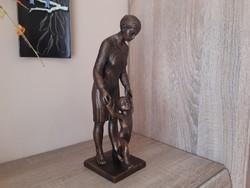 Bronzirozott képcsarnokos szobor.