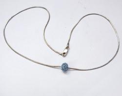 Ezüst nyaklánc, kristályokkal kirakott medállal.