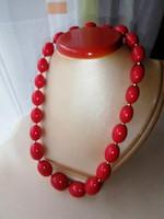 Piros színű retro divat ékszer, nyaklánc. A szemek között arany színű kis tavtartók vannak.