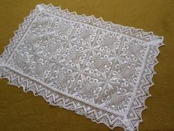 Fehér selyemmel hímzett csipkés kis terítő.