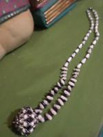Kicsit art deco-s , kicsit törzsi-amulettes hatású , üveg és gyöngyház gyöngyökből álló nyaklánc .