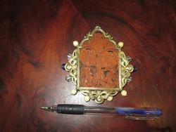 Fából faragott miniatűr oltár, ezüst nyakba akasztható keretben.