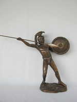 Metal statue of an ancient soldier throwing a spear