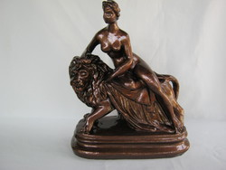 Large nude plaster sculpture on the back of a female nude lion