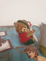 Old clipped teddy bear in Mr. green hat